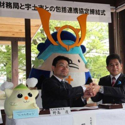 協定を締結し,がっちり握手する野島透九州財務局長(左)と元松市長の写真です